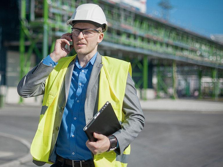 Architekt wbiałym kasku rozmawia przez telefon